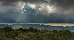 Alguns raios de luz do sol deslizam entre as nuvens de tempestade fotos de stock