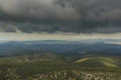 Alguns raios de luz do sol deslizam entre as nuvens de tempestade Foto de Stock