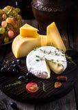 Alguns tipos de queijo em uma placa de desbastamento Ainda vida no estilo rústico Fundo de madeira escuro velho Imagem de Stock