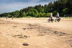 Alguns turistas em bicicletas em uma praia imagem de stock royalty free