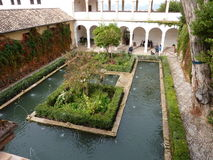Alhambra architecture. Photo of a pool inside the famous arabic Alhambra fortress in Granada, Spain surrounded by tourists royalty free stock photos
