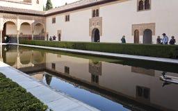 Alhambra Court of the Myrtles Longer Side. Tourists visiting the Court of the Myrtles along the central pool, in The Alhambra, Granada, Spain stock image
