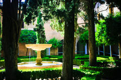 Alhambra- Courtyard Garden. A beautiful pedestal fountain is the centerpiece of this romantic hidden garden in the Moorish palace of the Alhambra in Grenada Stock Photo
