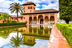 Alhambra - Granada, Andalusia, Spain. Granada, Spain - Nice view across a small pool and garden at Partal Palace, in the famous Alhambra in Andalusia stock image