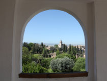 Alhambra Granada Spain. Alhambra seen through a window in the Generalife gardens. Santa Maria church bell tower. Granada Spain Stock Photography