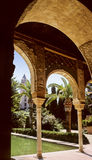 Alhambra palace. A view showing decorated pillars arches and ceiling, then gardens with palm trees of famous Alhambra palace, Granada, Andalusia, Spain Stock Photography