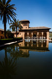 Alhambra Pavilion reflecting pool and tower. The pavilion with an arched portico by a pool and tower with palm trees in the garden at the Palacio del Partal in stock photos