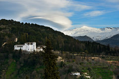 Alhambra and snowing Sierra Nevada mountains under a lenticular Royalty Free Stock Image