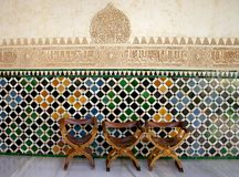 Alhambra Three Chairs. Three chairs located along a wall inside the Alhambra, which is located in Granada, Spain Royalty Free Stock Images