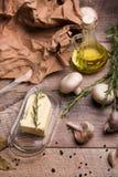 Alho, cogumelos, manteiga, alecrins e azeite em um fundo de madeira Um papel amarrotado e folhas de louro na mesa Imagens de Stock