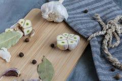Alho cortado fresco em uma placa de corte de madeira com pimenta colorida e a folha de louro prontas para flavor o molho Fotografia de Stock Royalty Free
