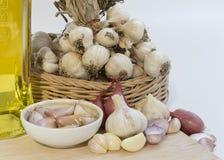 Alho, cravos-da-índia de alho, óleo e cebola no fundo branco Imagens de Stock Royalty Free