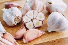 Alho, cravos-da-índia de alho e bulbos cortados do alho no backgrou de madeira Foto de Stock