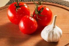 Alho e três tomates brilhantes com gotas da água Fotos de Stock