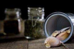Alho nas madeiras e nas especiarias em uma tabela de madeira Cravos-da-índia de alho na mesa de cozinha Imagens de Stock Royalty Free