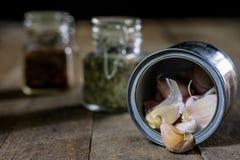Alho nas madeiras e nas especiarias em uma tabela de madeira Cravos-da-índia de alho na mesa de cozinha Fotos de Stock