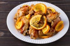 Ali di pollo agrodolci con le arance, servite con sesamo sul piatto bianco Fotografia Stock