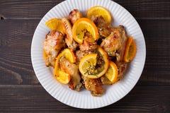 Ali di pollo agrodolci con le arance, servite con sesamo sul piatto bianco Immagine Stock