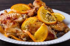 Ali di pollo agrodolci con le arance, servite con sesamo sul piatto bianco Fotografia Stock Libera da Diritti