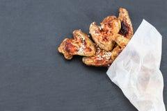 Ali di pollo al forno su fondo scuro con lo spazio della copia Vista superiore fotografia stock libera da diritti