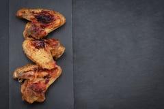 Ali di pollo al forno su fondo scuro con lo spazio della copia Vista superiore immagini stock libere da diritti
