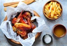 Ali di pollo arrostite con le patate fritte in una ciotola di legno sui precedenti di alluminio Immagine Stock