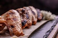 Ali di pollo arrostite su uno spazio di pietra nero del piatto per testo immagine stock libera da diritti