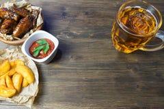 Ali di pollo con salsa fragrante e pungente con i semi di sesamo Un vetro di birra fredda fresca e delle patate fritte con il pom Fotografia Stock Libera da Diritti