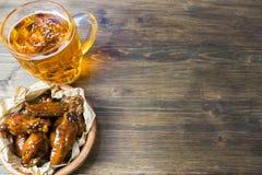 Ali di pollo con salsa fragrante e pungente con i semi di sesamo Un vetro di birra fredda fresca e delle patate fritte con il pom Fotografia Stock