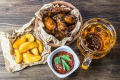 Ali di pollo con salsa fragrante e pungente con i semi di sesamo Un vetro di birra fredda fresca e delle patate fritte con il pom Immagine Stock