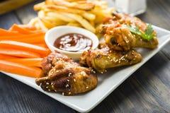 Ali di pollo con sesamo circondato dalle fritture e dalle carote Immagini Stock