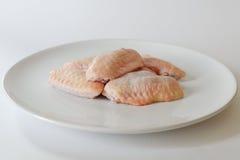 Ali di pollo crude fresche sul piatto bianco con fondo bianco Immagine Stock