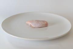 Ali di pollo crude fresche sul piatto bianco con fondo bianco Fotografia Stock Libera da Diritti