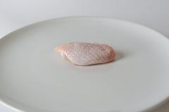 Ali di pollo crude fresche sul piatto bianco con fondo bianco Fotografia Stock