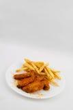 Ali di pollo e patate fritte calde Fotografia Stock