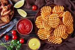 Ali di pollo fritto e patata croccante fotografie stock