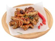 Ali di pollo grigliate sul tagliere di legno isolato su fondo bianco fotografia stock