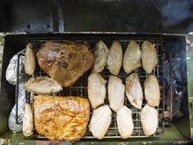 Ali di pollo di vista superiore e spalla di maiale che griglia su un fuoco di fumo fotografia stock libera da diritti