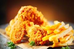 Ali e gambe di pollo fritto sulla tavola di legno immagini stock libere da diritti