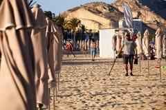 ALIACNTE SPANIEN, CIRCA JULI 2018 män med en metalldetektor på stranden arkivbild
