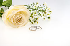 Aliança de casamento com o isolado da flor da rosa e do cortador do branco no branco Foto de Stock