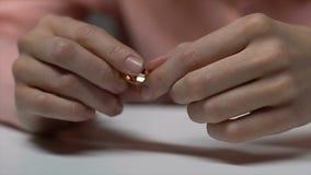 Aliança de casamento da terra arrendada da mulher, pensando sobre o divórcio, enganando-se na união filme