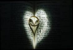 Aliança de casamento na Bíblia cercada pela luz do coração imagens de stock royalty free