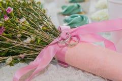 Aliança de casamento no ramalhete floral da fita cor-de-rosa foto de stock royalty free