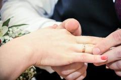 Aliança de casamento vestindo do homem no dedo da noiva Fotografia de Stock