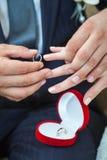 Aliança de casamento vestindo do noivo no dedo da noiva Imagem de Stock