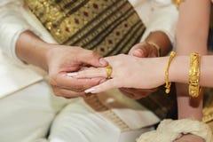 Aliança de casamento vestindo do noivo para sua mão da noiva Imagens de Stock Royalty Free
