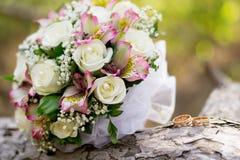 Alianças de casamento bonitas com o ramalhete das flores Declaração do amor, mola Cartão de casamento, cumprimento do dia do ` s  fotografia de stock royalty free