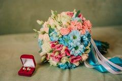 Alianças de casamento bonitas do ramalhete e do ouro do casamento em uma caixa vermelha Foto de Stock Royalty Free