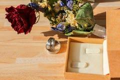 Alianças de casamento com cor-de-rosa seco e flor e caixa no backgro de madeira fotos de stock royalty free